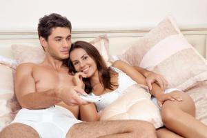 happy-couple-watching-tv-bedroom